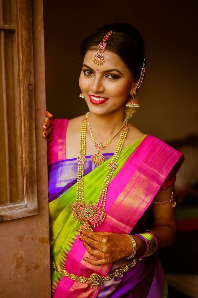 South Indian bride. Gold Indian bridal jewelry.Temple jewelry. Jhumkis. Pink,purple and parrot green silk kanchipuram sari.Braid with fresh jasmine flowers. Tamil bride. Telugu bride. Kannada bride. Hindu bride. Malayalee bride.Kerala bride.South Indian wedding.