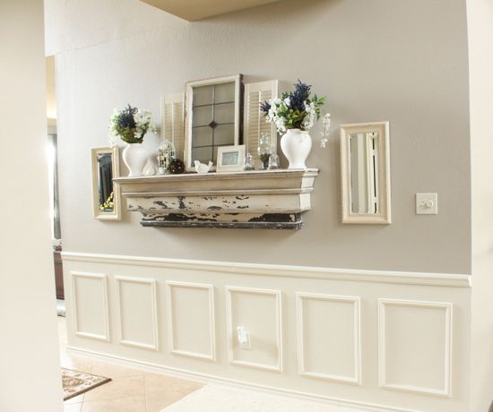 This is the finished product and we created the look of wainscoting by first adding a chair rail from Lowe's using a nail gun, painted the wall in a semi-gloss white paint (the same as our trim color), and added the boxes, also with a nail gun.