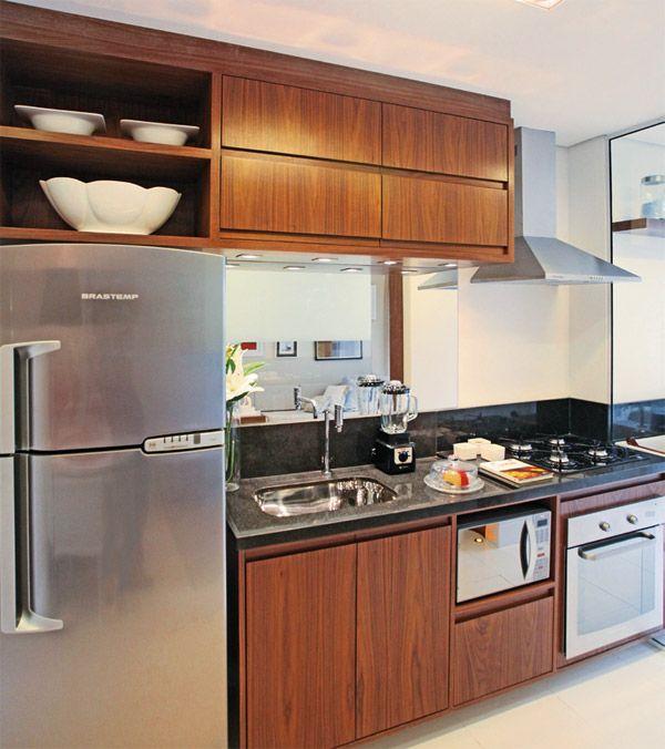"""A arquiteta Camila Klein optou pelos puxadores estilo cava, para baratear o custo da intervenção, e incluiu luminárias minidicroicas embutidas, que deram charme à composição. Além disso, aplicou recortes sob medida na marcenaria para os eletrodomésticos. """"O móvel sob medida é uma ótima solução. Por ser um apartamento pequeno, é indispensável o aproveitamento de espaços"""", ressalta Camila. O restante da iluminação é feito por um spot de sobrepor de acrílico com lâmpada dicroica."""