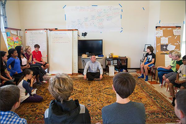 Student Guide Kelley Gary, center, leads a group discussion at Acton Academy in Austin, Texas. Roughly 30 students make up the Middle School Studio, a one-room environment where students are self-directed in their academic progress.