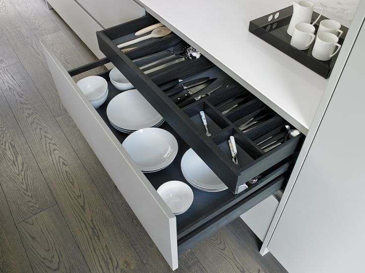 Handleless drawers finished in Zoffany Double Silver matt lacquer with charcoal oak interiors. Deep lower drawer for crockery storage and narrow cutlery drawer built-in organiser.