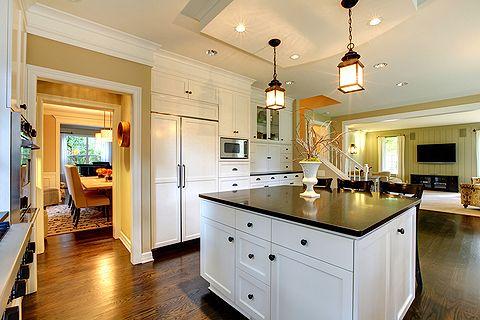 Moderne amerikanische Küche mit zentraler Kücheninsel und offenem Durchgang zum Wohnzimmer