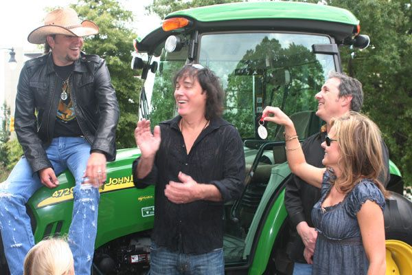 Jessica Aldean presents keys to the green tractor to her husband, Jason, as David Lee Murphy and Jim Collins look on.