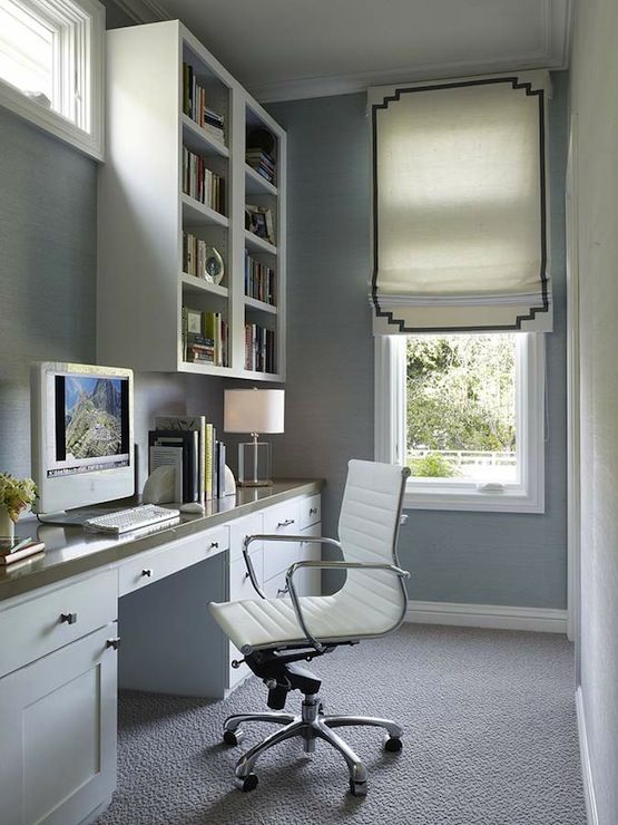 Long and narrow office with blue grasscloth wallpaper framing white cabinets with gray countertops. Home office with built-in desk paired with Eames Management Chair and white and gray fretwork roman shade and cornice box.