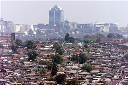 General view of Alexandra township, commonly known as Alex, a slum overlooking the Sandton sky scrapers in Johannesburg August 23, 2002. REUTERS/Juda Ngwenya