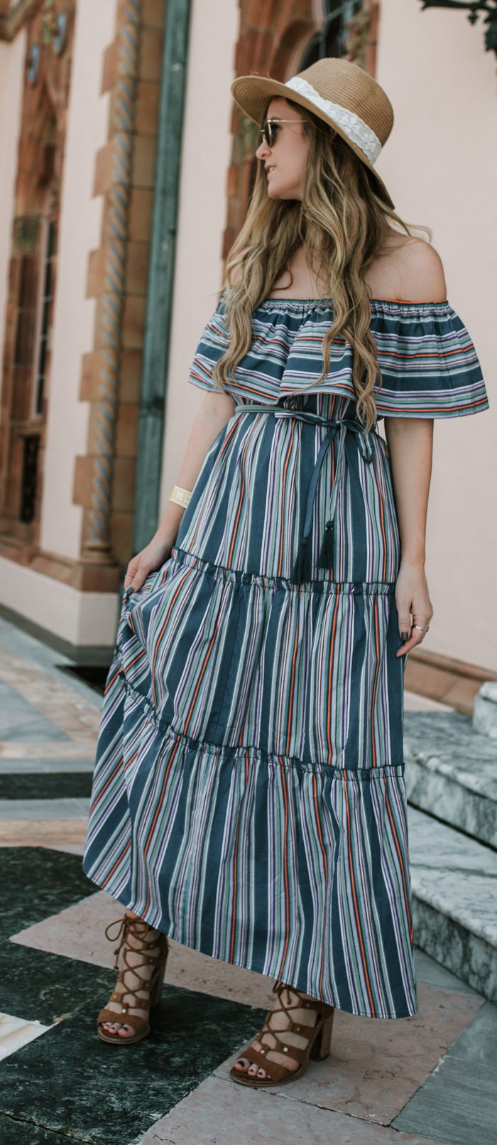 Cute vacation outfit styled with striped off the shoulder maxi dress, lace up block heel sandals, and straw hat