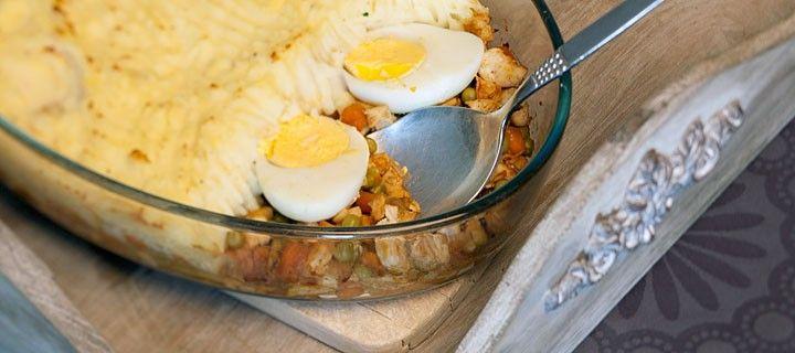 Authentiek Indische recept met kip, wortel, erwtjes en eieren onder een laagje aardappelpuree.
