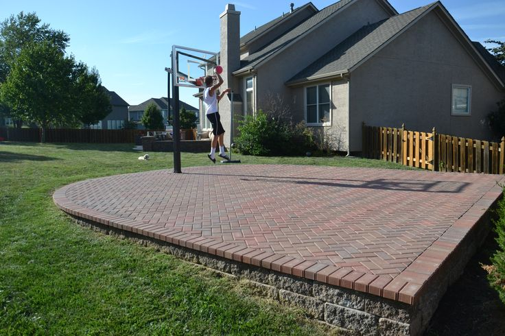 An attractive way to have a sport court in your backyard using interlocking pavers and segmental retaining walls.