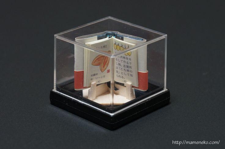"""豆本工房わかいの豆本。『能登のおいしいもの』。能登半島のおいしいものをイラストで紹介。大きさ縦38mm×横28mm。 The miniature book of Bookbinder WAKAI. """"The delicious thing of Noto."""" The delicious thing of Noto-Hanto is introduced with an illustration. Sizes are 38 mm x 28 mm."""