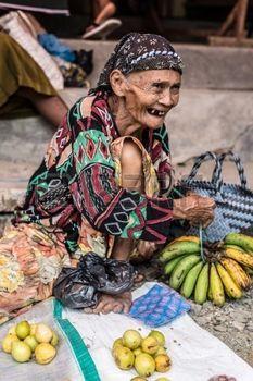 vendor: Donggala, Sulawesi, Indonesia - 1 settembre, 2014: Ritratto di un venditore di frutta rugosa vecchia donna in abiti tradizionali, seduta e sorridente al mercato locale di Donggala, Sulawesi centrali, Indonesia. Editoriali