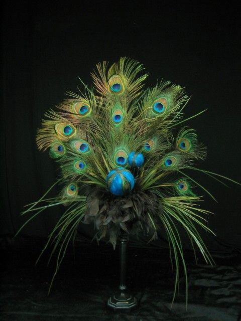 This exotic inspiration features two blue peacock feather balls surrounded by peacock feathers, grasses and brown chandelle feathers. The arrangement is crafted on a brown metal look, resin pedestal. The pedestal is 12 tall with a base diameter of 4. The entire arrangement is 30 tall,