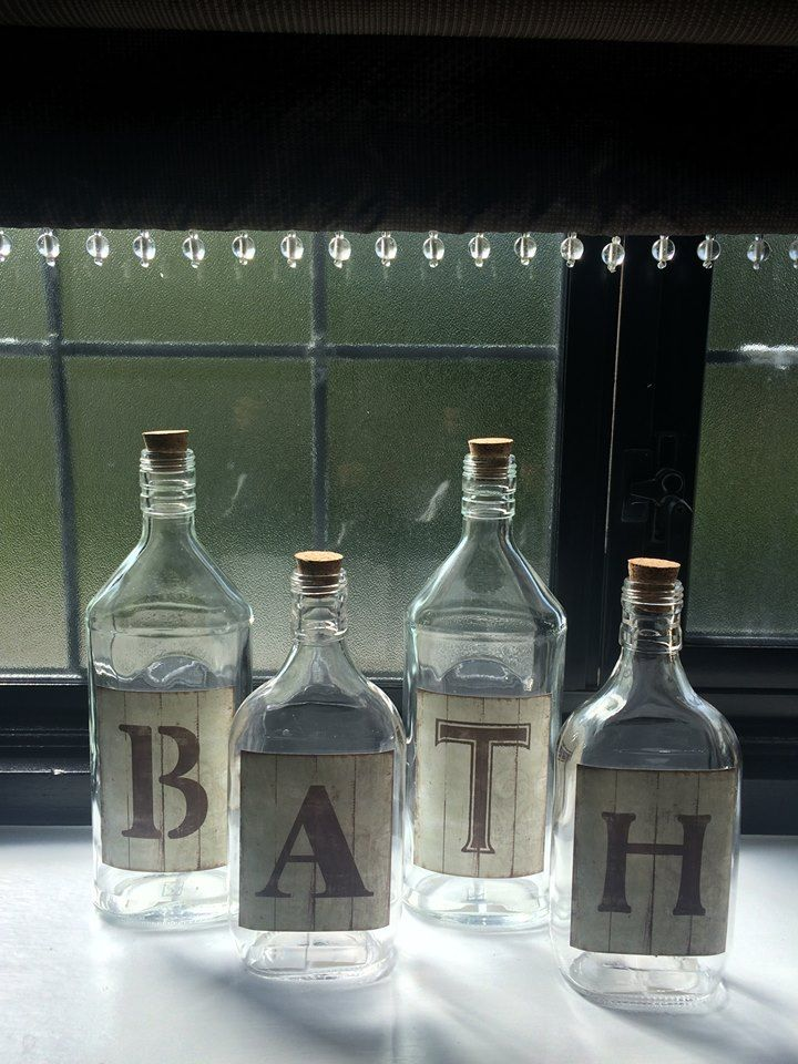 Bathroom accessories | elegant bath bottles underneath a chocolate brown roman blind with beading on the bottom edge.