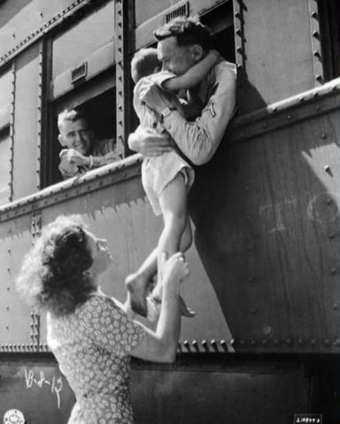 A soldier's wife hoists her son up to a train window for one last good-bye hug from his dad. #1940s