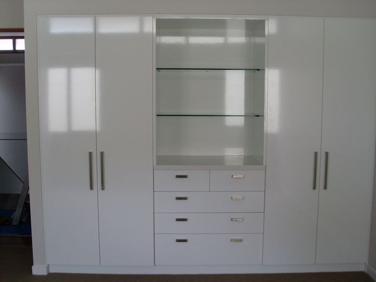 Custom white wardrobe cabinetry in bedroom with glass shelving