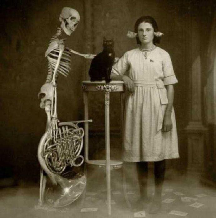 Винтажная фотография девочки и скелета из шкафа с черным котом по середине.