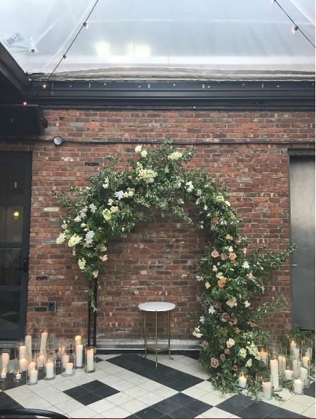 A large floral arch for an industrial wedding ceremony.   Poppies & Posies