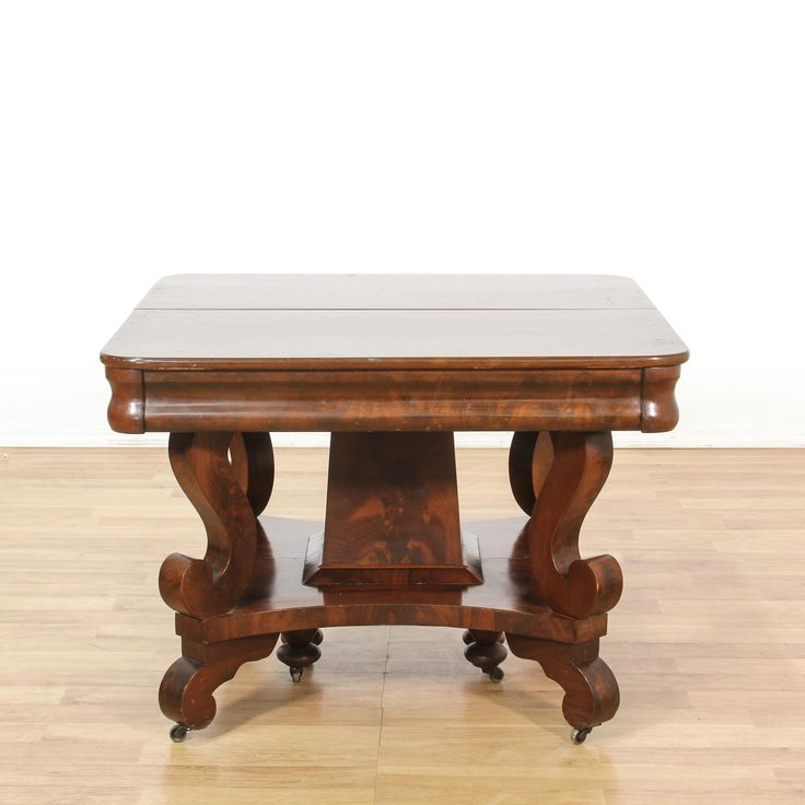 This empire style dining table is featured in a solid wood with a glossy flame mahogany finish. This dining table has a scroll leg base with curved edges and a rolling caster wheel base. Stunning table perfect for formal dining! #americantraditional #tables #diningtable #sandiegovintage #vintagefurniture