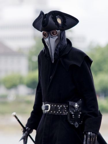 plague doctor. Love the look.  The walking cane, trench, pirate hat, gloves. even the mask though I think that might be the accessory Chanel might advise doing without.