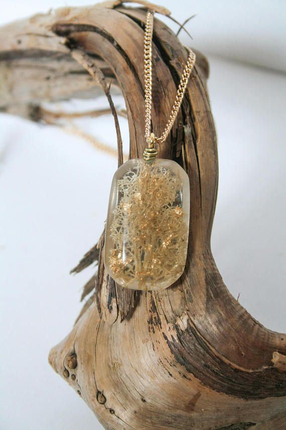 Pressed and dried white reindeer moss, encased in a clear rectangular gem-shape resin pendant with gold leaf flakes.   All pieces are made one at a time and entirely by hand, embedded with locally sourced objects. Each piece is sanded from 220 to 3000 grit and polished to a high shine.