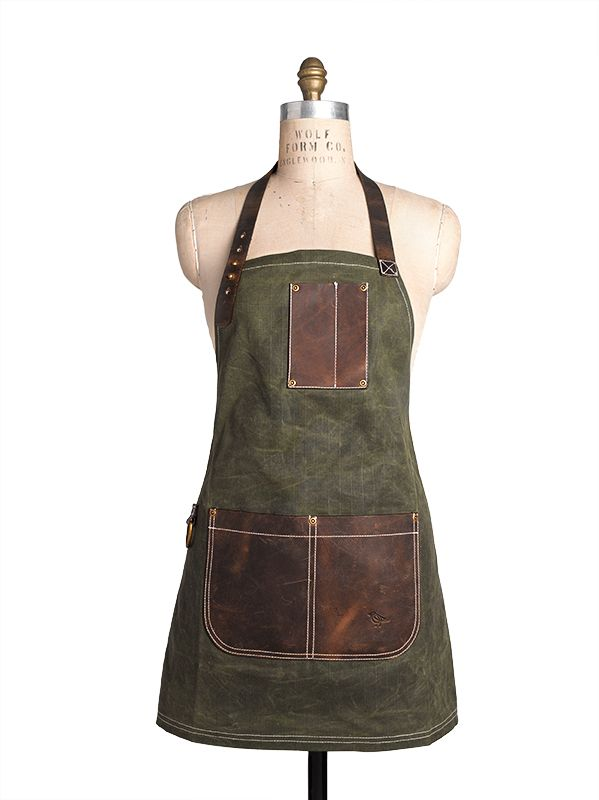 "AS SEEN IN THE MAY/ JUNE 2014 ISSUE OF NEW YORK SPACES MAGAZINE! From the Birdkage Utility collection, inspired by rugged American tradition.  The ""Peyton"" style is made of waxed heavyweight cotton canvas with a distinct ""grid"" pattern, and trimmed with heavy-duty saddle leather.  Our mini bib Apron is roomy on the sides, and is […]"