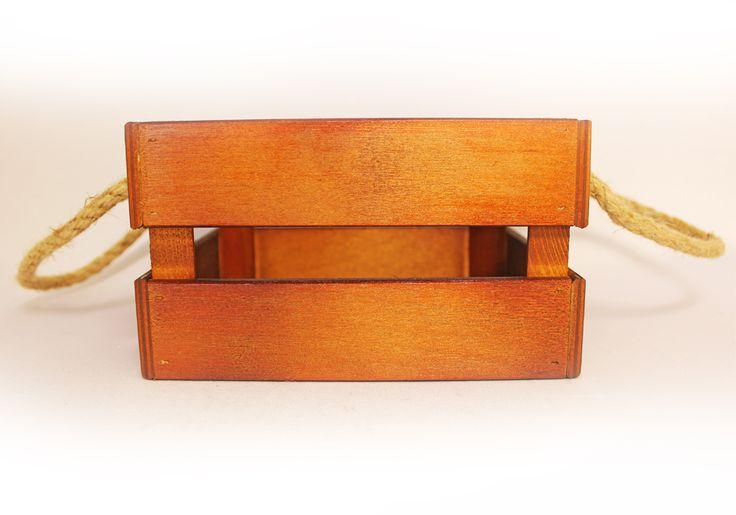 Деревянный ящик с ручками из шпагата имеет размер в длину 17,5 см, в ширину 15 см, в высоту 10 см. Донышко выполнено из МДФ, боковые стороны из фанеры, углы укреплены при помощи брусков. Ящичек окрашен морилкой по дереву, это придает ему натуральный коричневый цвет. Ящик используется, как функциональный предмет декора интерьера. В него можно поместить различные предметы, например, небольшие игрушки, книжки, баночки, хозяйственные мелочи и др.