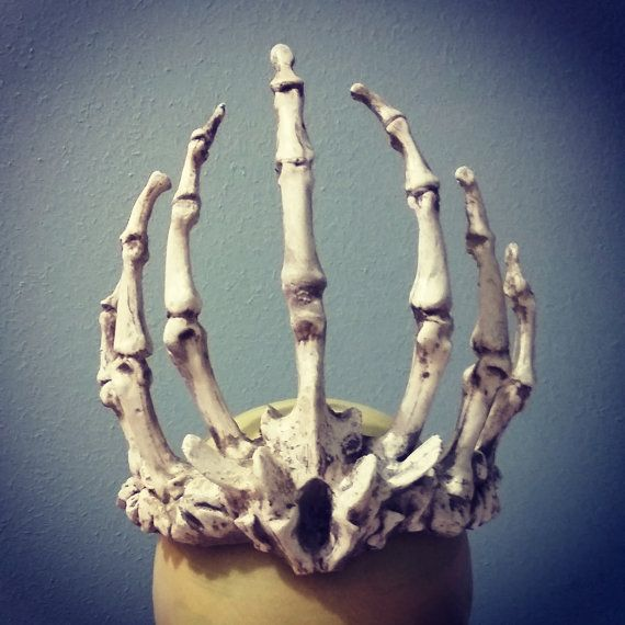 This is a listing for a crown of finger bones. It is made of resin, rubber, urethane foam, and ribbon. It is lightweight and attaches with a