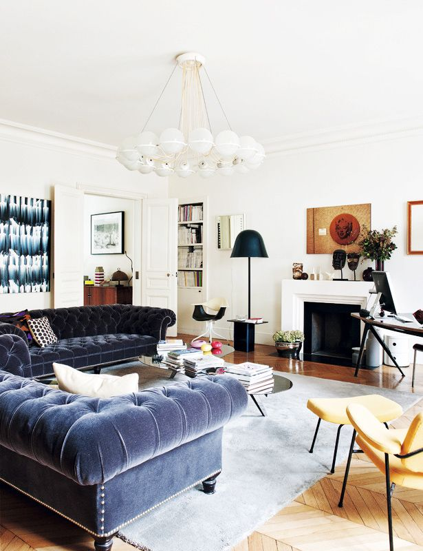 White living room with blue velvet chesterfield sofas, modern accessories
