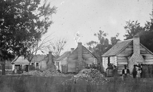 Port Royal, South Carolina, slave quarters, 1862.   Taken in 1862, when freedom came to the Gullah in the area of Beaufort and St. Helena, this photo shows a row of slave quarters. This grouping is very unusual for quarters before emancipation, because they are not in a straight row. They are relatively well built, with brick chimneys. The areas between the houses are fenced, indicating a level of personal and family space defined in the grouping. The man in the foreground is sitting on a…