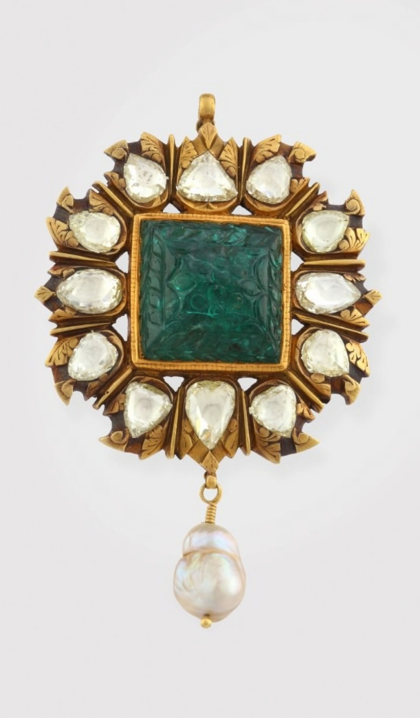 This pendant centers on a beautifully carved square shaped emerald, with a surround of rose cut diamonds, set in gold, and suspending a single baroque pearl drop. The stunning carved sugar loaf cut emerald weighs approximately 25 carats, and the total diamond weight is approximately 9.50 carats. The emerald is rare for its size and color.