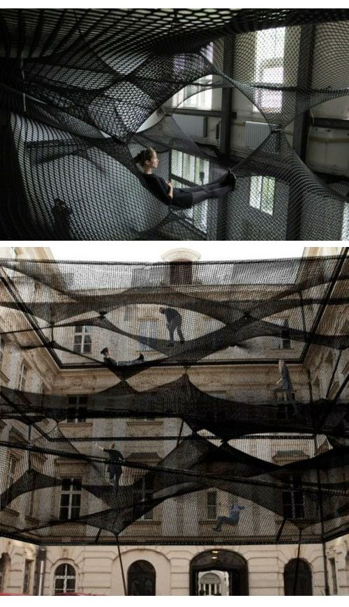 """Net by design collective Numen consists of multiple layers of flexible nets suspended in the air. The flat layers of the net are subsequently connected to one another on counterpoints thus forming a """"floating landscape"""" open for visitors to climb in and explore."""