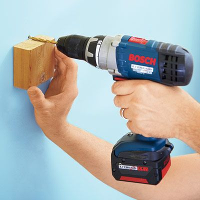 Drill perfectly perpendicular holes using a wood block as a guide. Cut one end of the scrap square. Using a combination square, draw a line perpendicular to the cut end. Hold the block against the wall and let the penciled line direct the drill bit at the target. Remove the block after the hole is under way.