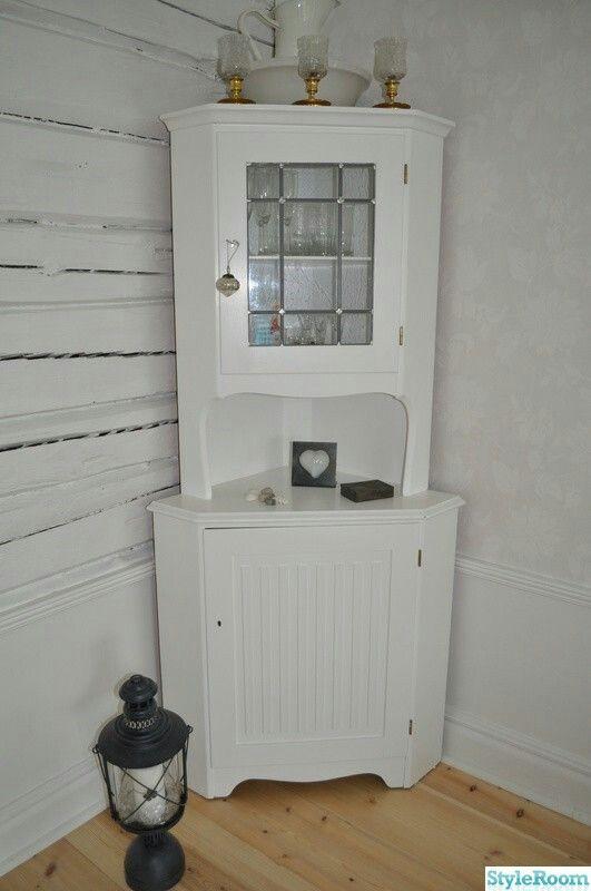 Begagnat hörnskåp mellan fönster och soffa