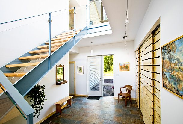 Gananoque Lake Road House - The large front entry is flooded with natural light from above.  The 15 foot long closet is enclosed with custom-made doors made from wood harvested on the property.  The oak treads on the stairs also come from the property.