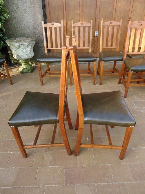 Fabulous set of twelve Arts & Crafts oak dining chairs by William Birch for Liberty & Co.  These originally had rush seats but now have been professionally upholstered in green leather and are much more comfortable and look just stunning with copper studs highlighting the