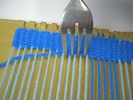 Weaving on a cardboard loom. This is how my 9-year-old son got us both into fiber arts!  Gotta love 4th grade art class . . .