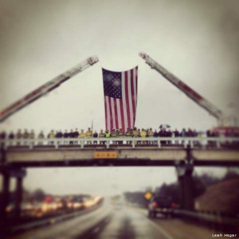 The flag is draped from two fire engine ladders on an overpass near Midlothian, Tx as Chris Kyle's funeral procession approaches. (Courtesy: Leah Hegar via Facebook