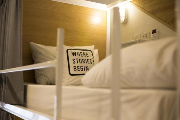 Bed One Block Hostel Design - where stories begin. This slimlined hostel design in Bangkok, Thailand is genius! I love these pillows, urging people to connect and make new stories :)