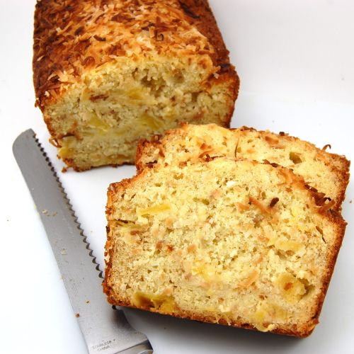 Coconut Pineapple Bread - Here is one bread you will want to include in your homemade holiday goodie bags. Coconut Pineapple bread speckled with chunks of pineapple and toasted coconut. With each bite of this scrumptious bread, you will be transported to a white sandy beach with your toes in the sand and a cold drink in your hand.