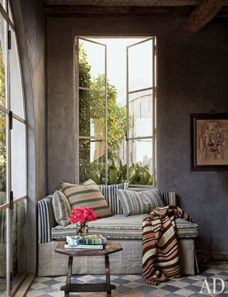 "For his beachfront retreat in Malibu, California, antiques dealer Richard Shapiro used plaster wall treatments resembling weathered stone to evoke ""the look, age, and aura of a very old, windswept structure from the Mediterranean or Aegean."" In the library, the look of the walls' rich finish varies widely depending on the light, making the space both inviting and mysterious 
