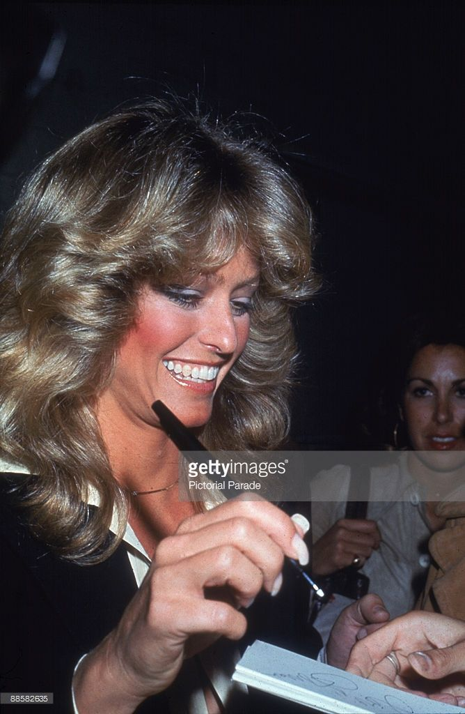American actress Farrah Fawcett (then known as Farrah Fawcett-Majors) smiles as she signs an autograph on the way out of the studio after taping an episode of the 'Merv Griffin Show,' November 1976.