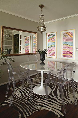 Bito Feris - Diseño y Decoración - Comedor con  alfombra diseño de cebra, sillas transparentes ghost de Starck, mesa blanca redonda. En el muro cuadros coloridos en tonos fucsias y turquesas; mientras que en el otro, ubicamos un espejo rectangular de marco dorado envejecido. Desde el techo cuelga una lámpara de lágrimas.