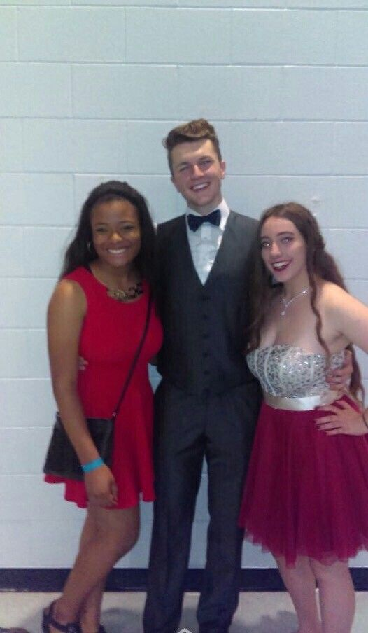 Homecoming feature! On the left is wearing a red knee length dress, with black flats. The male is wearing a black suit with a white shirt, black bow tie and black dress shoes. On the right is wearing a knee length silver and red dress with silver flats.