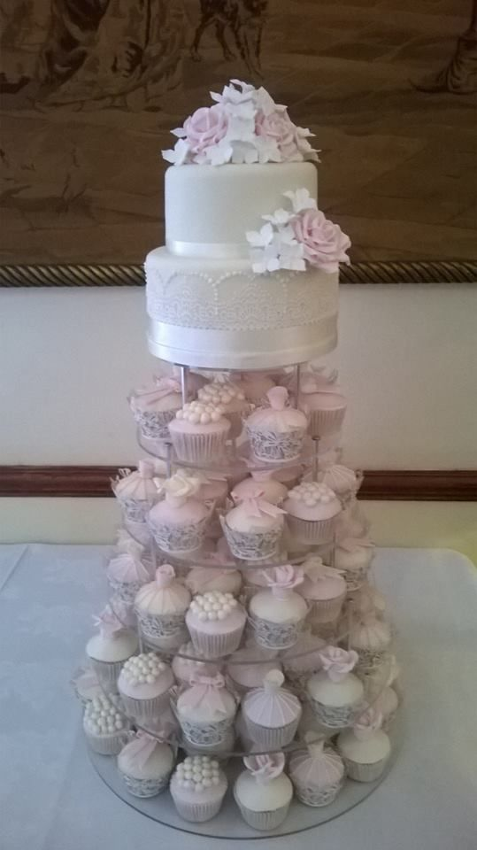 We worked really hard to create all of these desserts for Emma and James!  We made a 2 tier traditional moist fruit cake soaked in brandy, decorated with sugar lace, roses and hydrangeas. Below that is a tower of lemon and vanilla cupcakes topped with icing and decorated with sugar roses, bows and pearls.  #fruit #cake #weddingcake #brandy #roses #icing