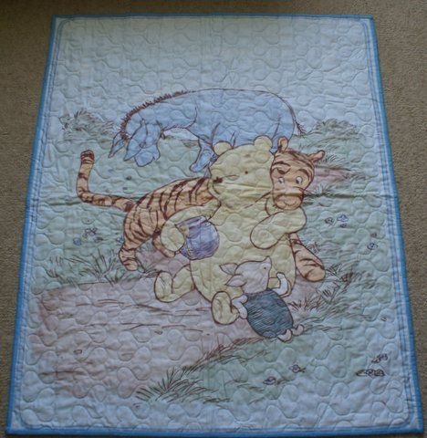 Australian Handmade Gifts - Winnie the Pooh Cot Quilt - $75 - https://www.highlandshandmade.com.au/winnie-the-pooh-cot-quilt-75/ - Winnie the Pooh Blue  The well known children's story.  100% cotton front and backing fabric with lightweight wadding.  Machine quilted with heart shapes. Washable with a gentle cycle.  Suitable for a little boy. Size 106 x 87 cms  Made in the Southern Highlands of country NSW by Dennis Buck.  Time taken to make this was 6 to 8 hours