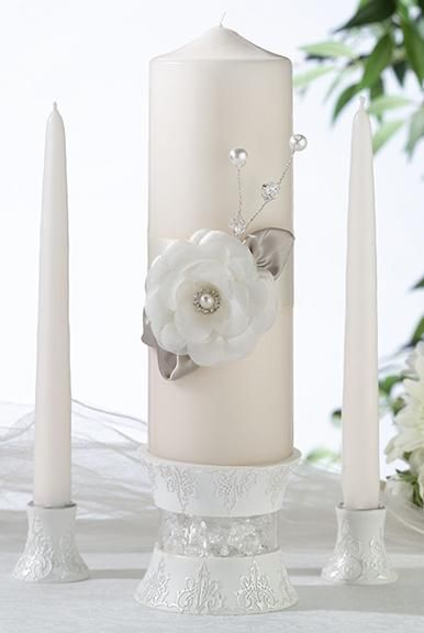 Taupe Rose Wedding Unity Candle Set includes a unity pillar candle and two matching taper candles. The unity candle features an ivory satin band in the middle. On the band sits a white fabric flower with a rhinestone center. It has two taupe colored satin leaves. There are also pearl and crystal decorations extending out from behind the flower on top. The candle holder set is not included.