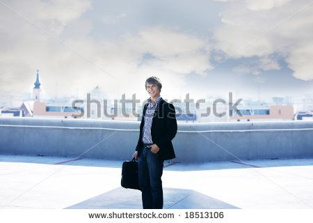handsome business man with briefcase on top of a building with city Cluj-Napoca as a background