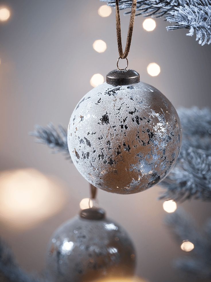 Create a unique and opulent look for your Christmas tree with our set of six silver leaf effect baubles, each with an elegantly distressed flocked finish. Featuring an antiqued brass fastener and faux suede hanging loop, these baubles will bring a touch of true luxury to your Christmas decor. Also available in a festive pinecone shape.