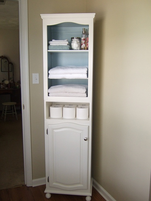 "I made this cabinet from 2 thrift store kitchen cabinets.  I built a simple box from 3/4"" mdf (just tall enough for toilet paper) to put in between the cabinets. The feet are round wooden drapery finials."