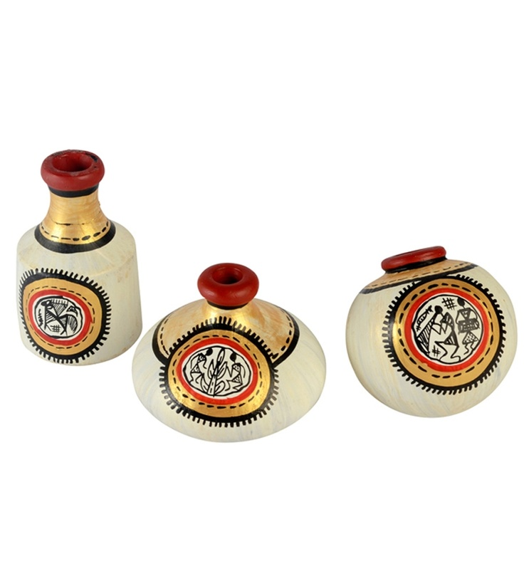 """Terracotta """"Warli"""" Handpainted Natural White Pots Natural (Set Of 3):-A very charming and ethnic off white and gold earthen miniatures set of 3 in terracotta in unique shapes with hand painting of working men on the pots with red and black paint. The red and gold border on the top makes the set look very beautiful when decorated tastefully. You can put these on a shelf or on your side table."""