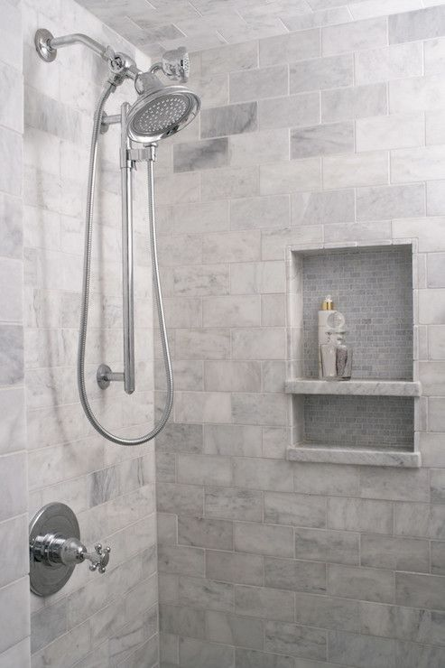 Walk-in shower with white and grey marble subway tiled surround and ceiling with mosaic tiled niche and dual shower head.